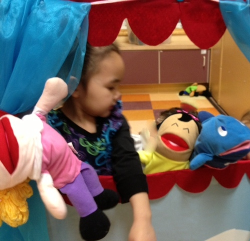 Gege playing with puppets at Head Start